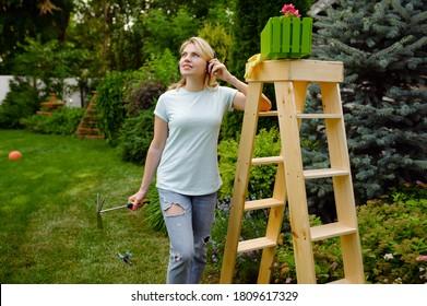 Happy woman looks on flower bed, gardening
