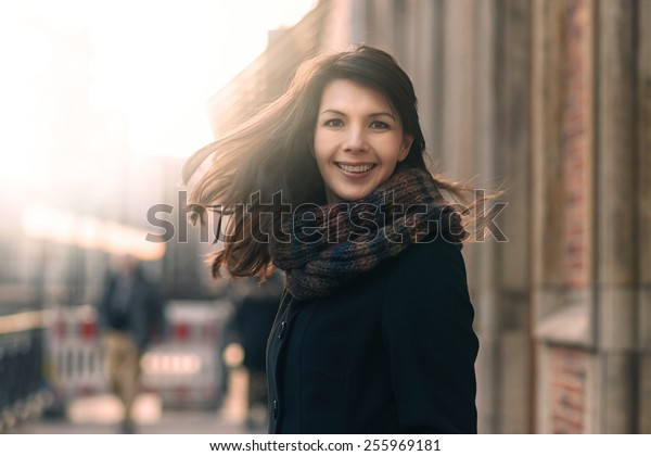 Happy woman with a lovely smile standing in her coat and scarf on an urban street in winter looking at the camera with a joyful expression and her hair blowing in the wind