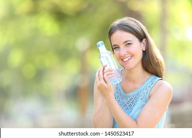 Happy woman loving a plastic water bottle in a park with a green background