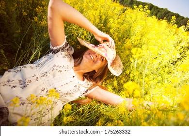 Happy woman lying among yellow wildflowers in summer
