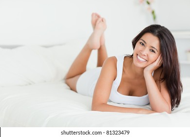 happy woman lying on bed with crossed legs looking into camera in bedroom