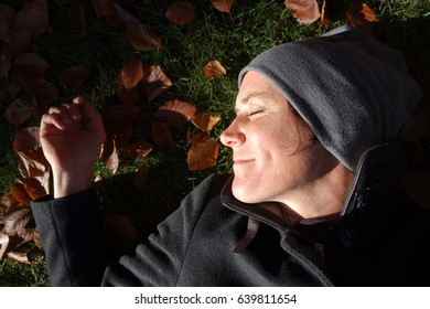 Happy woman lying on the grass in the sunlight