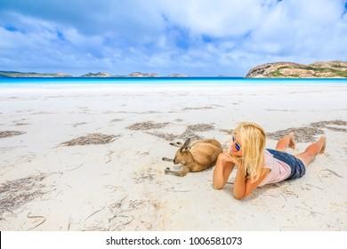 Happy woman lying on pristine white sand of Lucky Bay near Kangaroo. Cape Le Grand National Park, Esperance, Western Australia. Female tourist enjoys one of the most paradisiacal Australian beaches.