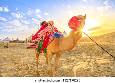 Happy woman lying over a camel on sand dunes of beach at Khor al Udaid in Persian Gulf, southern Qatar. Caucasian tourist enjoys camel ride at sunset, a popular tour in Middle East, Arabian Peninsula