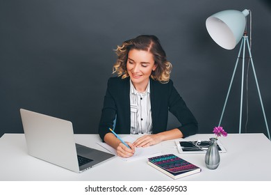 Happy Woman makes notes in her notebook.Girl at the office,woman in black jacket,curly hair,working space,white background,busy,office manager,best worker,businesswoman,new idea,happy,emotions
