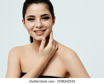 happy woman with makeup on face touching face with hand