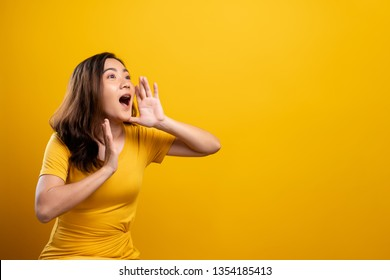 Happy woman making shout gesture isolated over yellow background