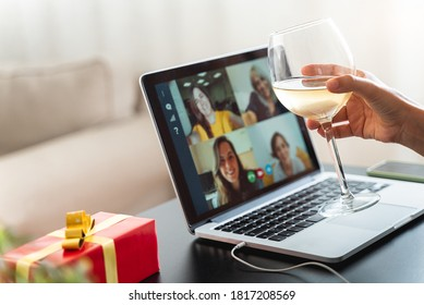 Happy woman making a toast on video call celebrating christmas with glass of wine online during coronavirus outbreak - Focus on wine glass
