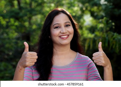 Happy woman making two thumbs up gesture at outdoors