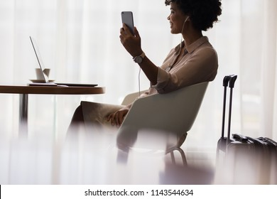 Happy woman making video call from mobile phone while sitting at airport lounge. Business woman waiting for flight at airport and using smart phone.