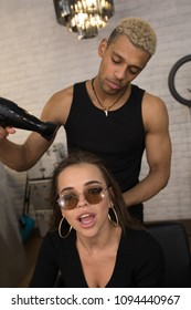 Happy woman and male hairdresser making hot styling at hair salon.