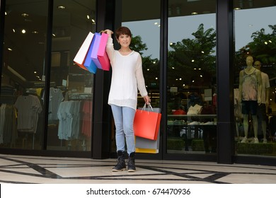 Happy woman at the mall holding shopping bags and smiling.