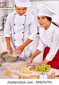 Happy woman and man in chef hat cooking dough .Grapes in foreground. Professional cooking in kitchen.