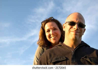 Happy woman and man (facing light at sunset - Models are 35 years old)
