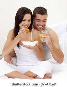 Happy woman and man having nutritive breakfast in bed