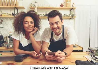 Happy woman and man holding phones at cafeteria