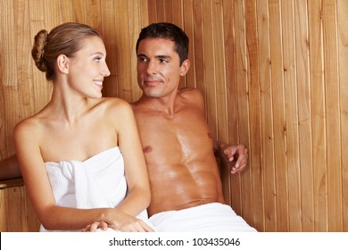 Happy woman and man sitting together in a sauna