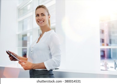 Happy woman manager holding touch pad and thinking about something good while standing in modern office interior,young smart female secretary smiling for someone during work on portable digital tablet