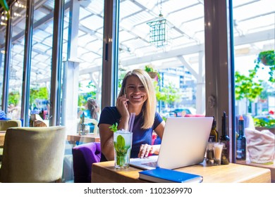 Happy woman marketing specialist talking on mobile phone, sitting with laptop computer in coffee shop. Cheerful female blogger having pleasant conversation via cell telephone during breakfast in cafe