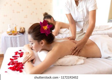Happy woman with masseur hand which rejuvenating spa having aroma therapy massage with essential oil, massage and people, beauty, spa, healthy lifestyle and relaxation concept at Spa salon