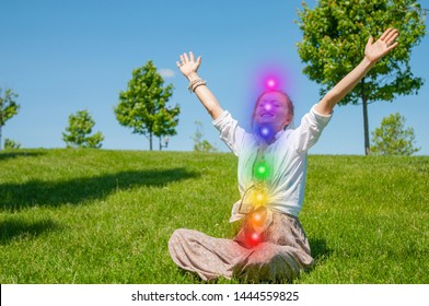 Happy woman is meditating in the lotus pose with glowing seven chakras on grass. Woman is practicing yoga on the park. Kundalini meditation.