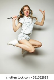 Happy woman with microphone jumping and singing
