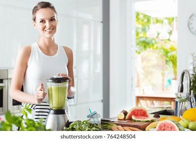 Happy woman mixing green vegetables in blender while preparing energetic cocktail