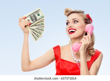 Happy woman with money, talking on phone, dressed in pin-up style dress in polka dot, on blue background. Caucasian blond model posing in retro fashion and vintage concept studio shoot.