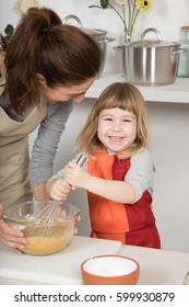 happy woman mother with glass bowl, and three years old child looking smiling and whipping with whisk, in teamwork, making and cooking a sponge cake at kitchen home,