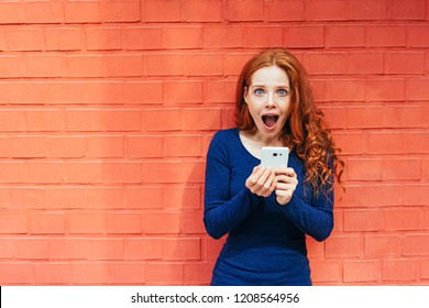 Happy woman with mouth open in amazement while she holds white smart phone and stands in front of brick wall