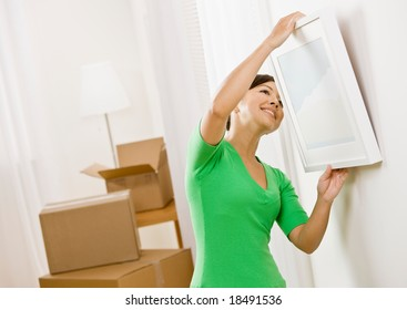 Happy woman moving into new home hanging picture on wall