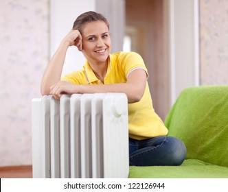 Happy woman near oil heater in home