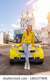 happy woman near yellow car in city in yellow clothes