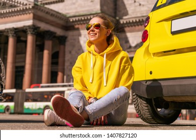 happy woman near yellow car in city in yellow clothes.