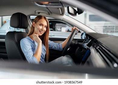 Happy woman new car owner sitting in driver seat