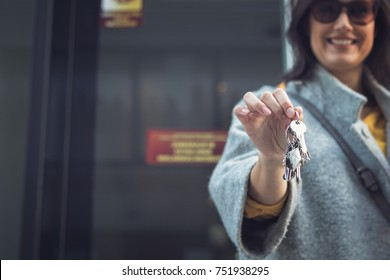 Happy woman with new house keys. Real estate agent showing keys of new apartment.