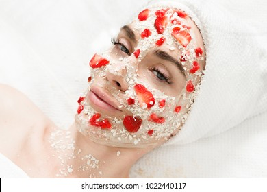 Happy woman with oatmeal & strawberry mask on her face