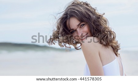 Happy woman on the beach. Portrait of the beautiful girl close-up, the wind fluttering hair. Spring portrait on the beach. Young pretty girl. Young smiling woman outdoors portrait. Close. ocean