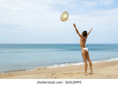 Happy woman on the beach is throwing her hat