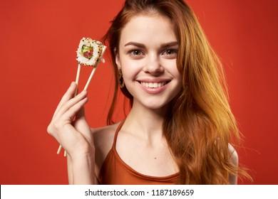 happy woman on chopsticks in sushi rolls