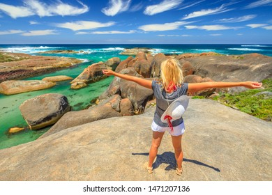 Happy woman on the cliffs above elephant-shaped rocks of Elephant Rocks in Western Australia. Young girl looking Great Southern Ocean in William Bay NP. Summer destination in Australia, Albany Region.