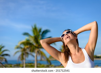Happy woman on tropical travel having fun. Caribbean vacation joy and freedom. Caucasian brunette model wearing sunglasses and looking up to clear blue sky.