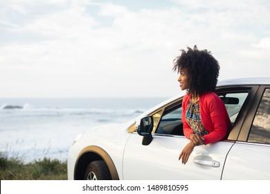 Fröhliche Frau im Urlaub, die von ihrem Auto aus den Blick auf die Küste genießt. Entspannte Sommerreise.