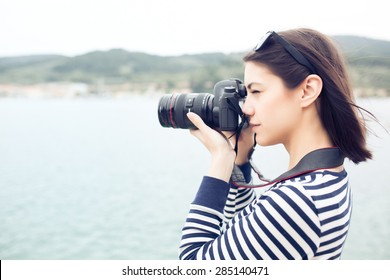 Happy woman on vacation photographing with a d slr camera on the  seaside beach.Vacation photography travel concept
