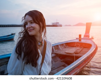 Happy woman on vacation in Thailand. Pretty young girl standing on the sunset beach in front of  traditional longtail fishing boat. Holiday trip on Phuket.