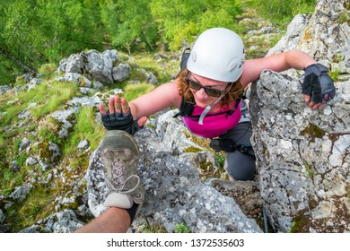 Happy woman on a via ferrata route at Baia de Fier, Gorj, Romania, near Women's Cave. Female climber, equipped with gloves, does a high five with another person's shoe.