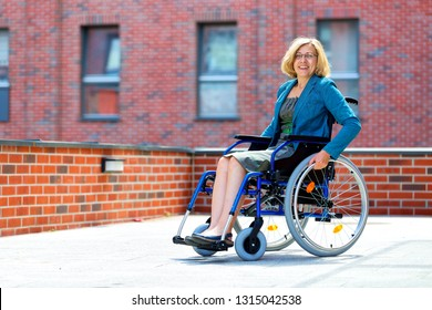 happy woman on wheelchair smiling surrounded by bricked walls and buildings
