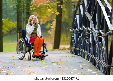 happy woman on wheelchair talking on the phone in the park