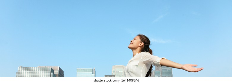 Happy woman with open arms in city sky panoramic banner breathing clean air for pollution concept lansdcape header. Asian lady in Asia with closed eyes.