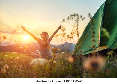 Happy woman with open arms seat near tent around mountains under sunset light sky enjoying the  leisure and freedom.
